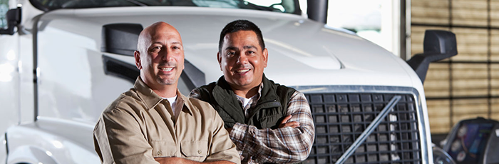 Two male truck drivers standing in from of a truck smiling