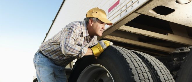 Male truck driver changing his tires