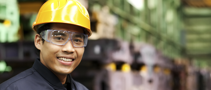 Smiling worker in hard hat and goggles