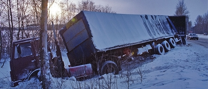 Transport truck on it's side by a snowy road