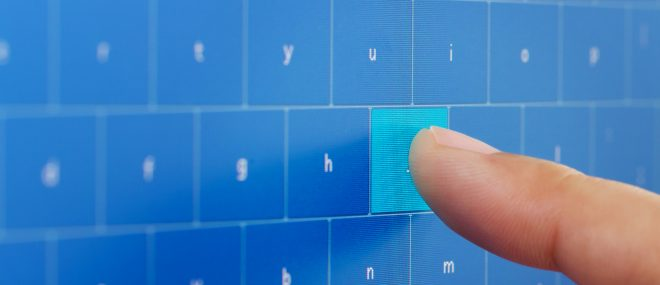 Human hand typing on digital keyboard at touch screen.