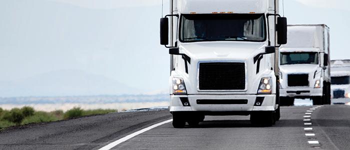 Three trucks driving on a highway