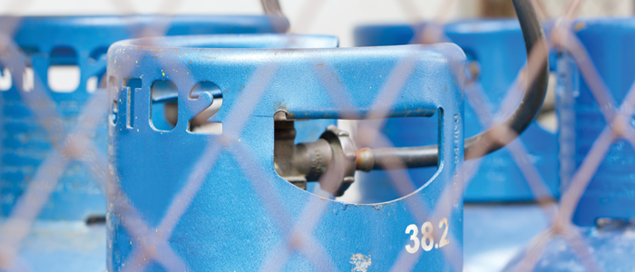 Compressed gas cylinders in a cage.