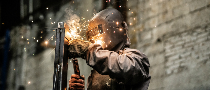 A man welding in a shop.