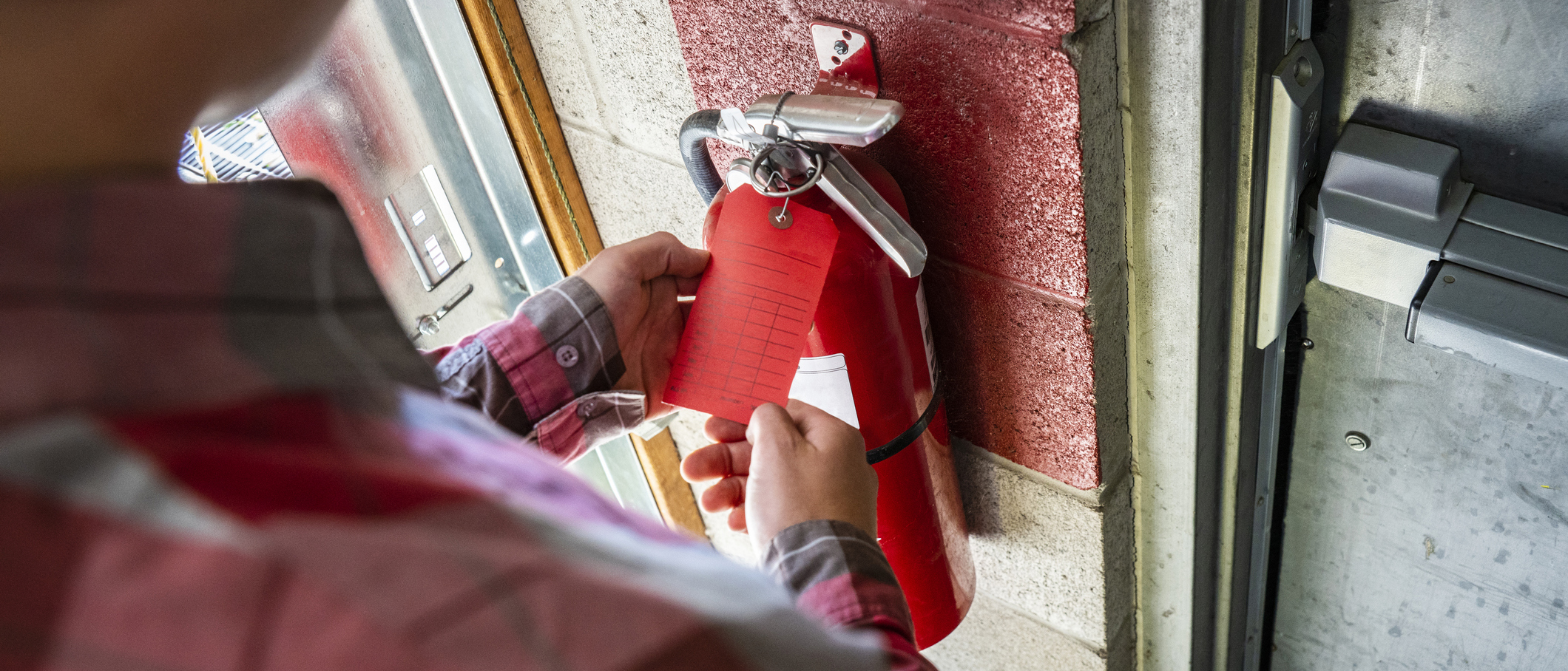 A person checks a fire extinguisher.