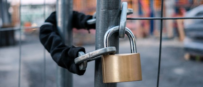 lock and chain on fence to prevent construction equipment theft.