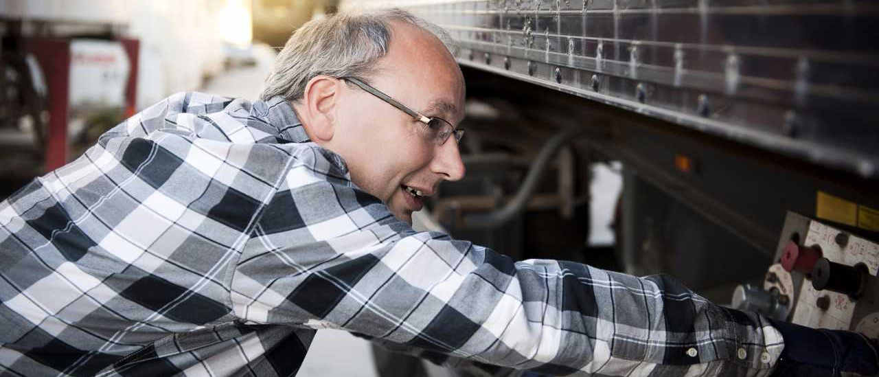 man performing a pre-trip inspection on a truck.