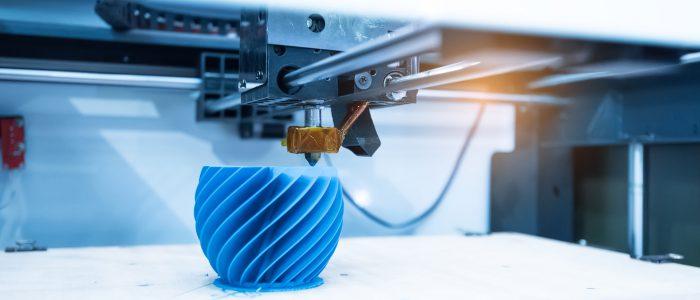 Photo d'une imprimante 3D imprimant un objet bleu