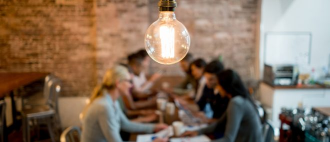 Brainstorming small business resources at a table under a light bulb.