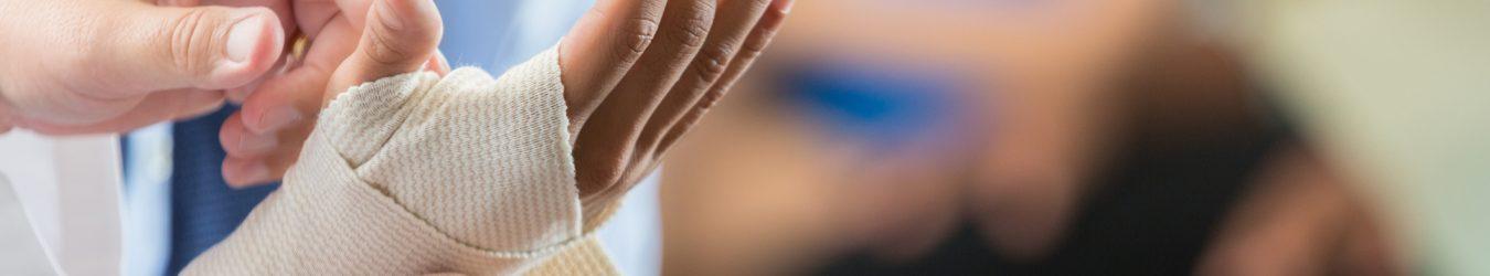Doctor bandaging a businessman's hand.