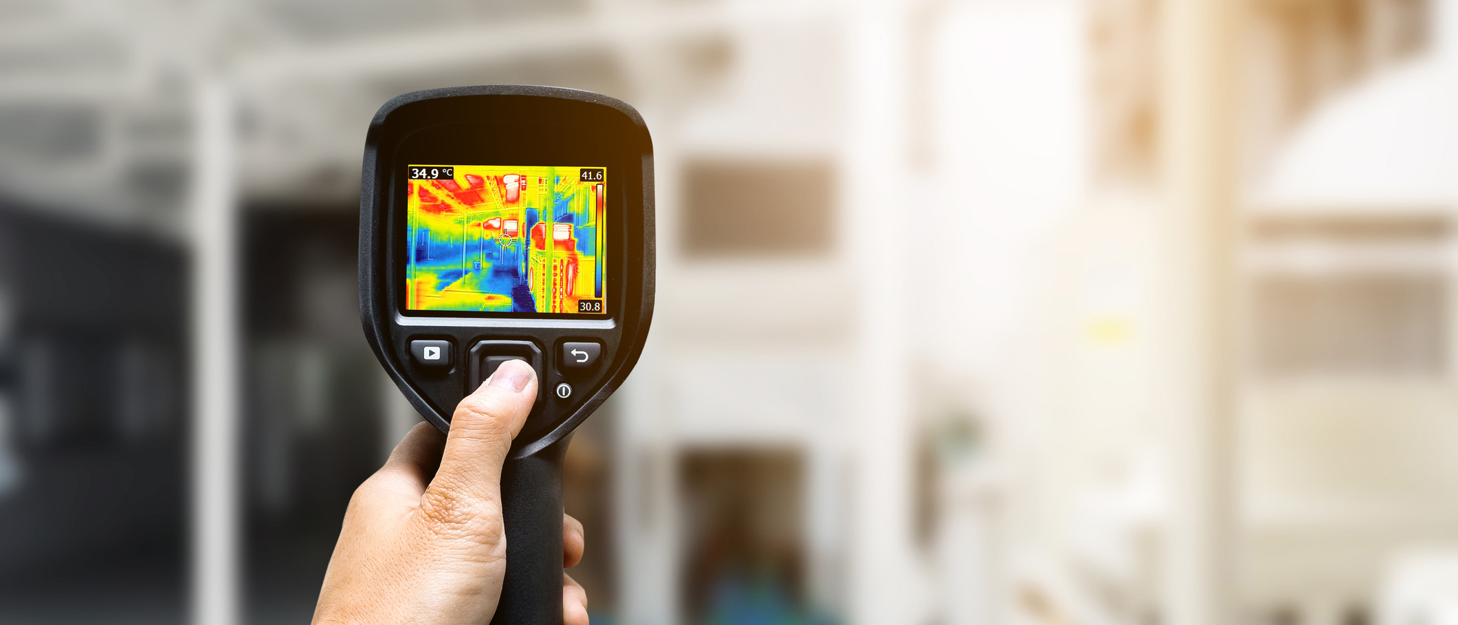 Technician using thermography camera to check temperature in factory