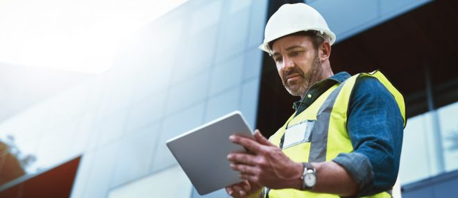 Construction manager checking his project funds on tablet