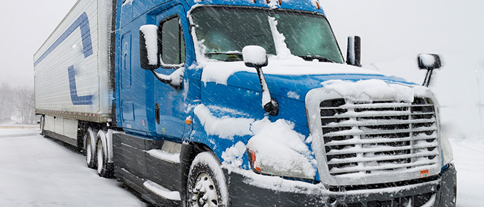 blue transport truck parked with snow accumulated