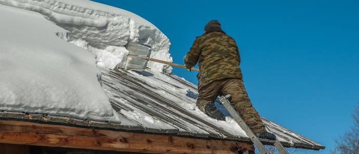Business owner removing snow from roof
