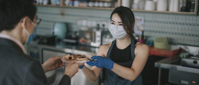A waitress wearing a mask.