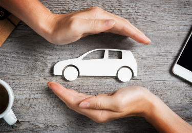 Two hands protecting car cutout over a wooden table.