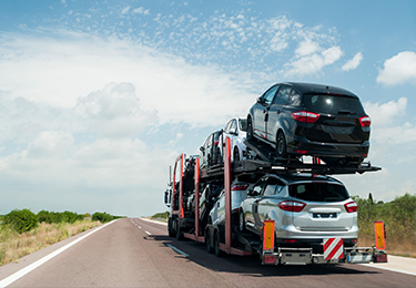 A truck with a car hauler trailer carrying a load of vehicles on a empty road.