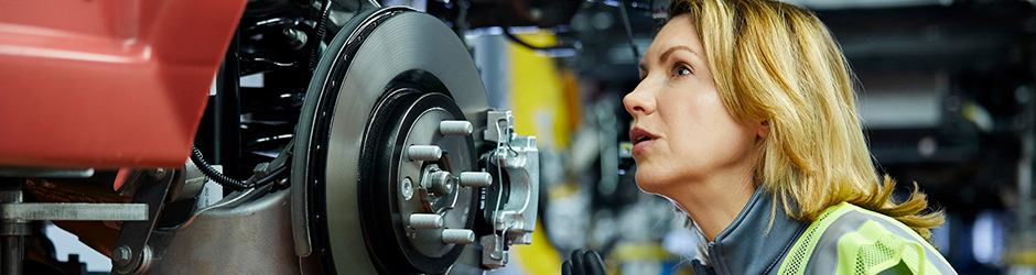 A female inspecting car parts.