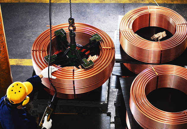 Worker using a mechanical lift on large spool of copper coil with two more copper coils on the side.