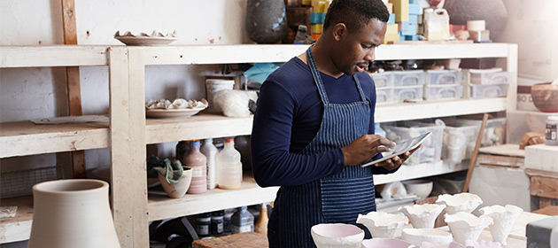 Male business entrepreneur working in his ceramics shop.
