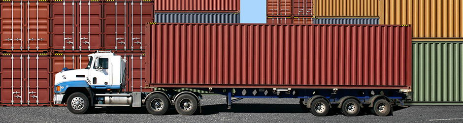 A freight container being loaded onto a truck at the docks.
