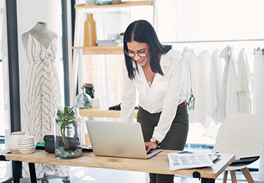 A female business owner standing over a desk, using her laptop at her clothing store.