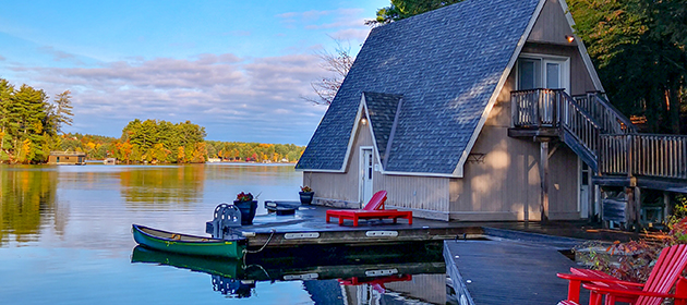 A-frame cottage by the water with a motorized boat