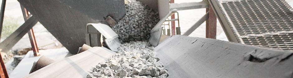 White concrete rocks on a conveyer belt.