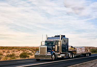 A long haul semi-truck carrying freight on a flatbed trailer.