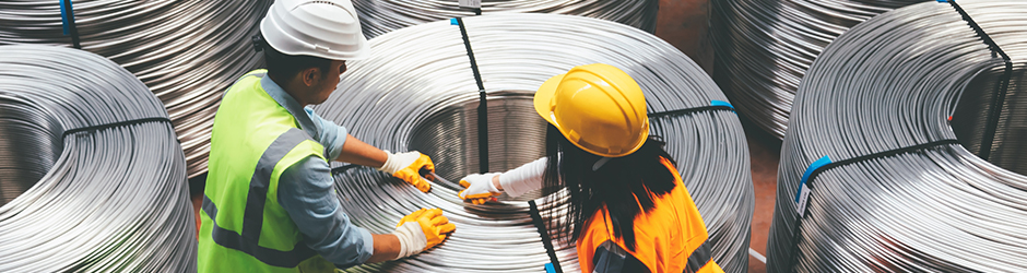 Two workers spooling metal wire in a manufacturing facility.