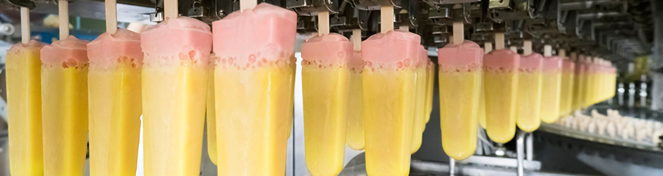 Freshly dipped ice cream popsicles on a conveyer belt.