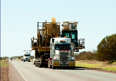 A white truck carrying a wide oversized cargo of heavy machinery.