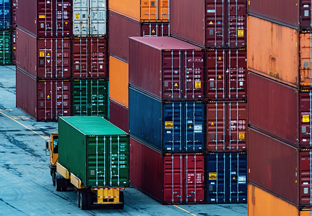 A truck transporting a shipping container with stacks of shipping containers nearby.
