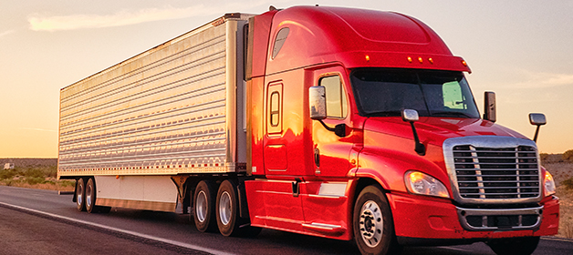 A big red rig semi-truck with an enclosed trailer transporting local goods on a roadway.