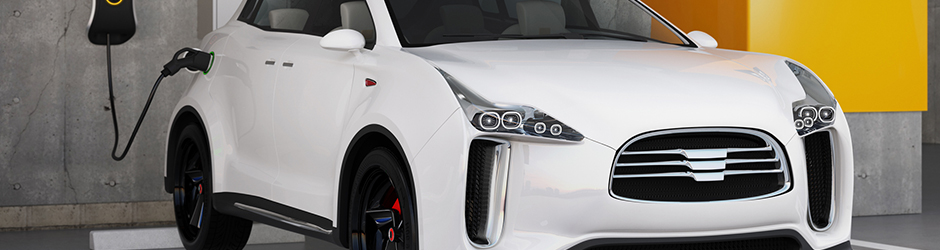 White electric car parked and plugged in an outlet inside a garage.