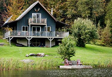 A cottage on a slopped grassy hill.