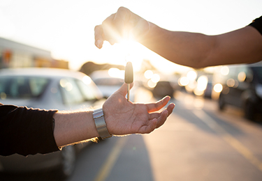 A person dropping car keys into another person's hands.