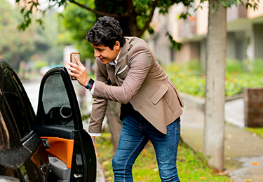 A person opening the passenger door of a black car.