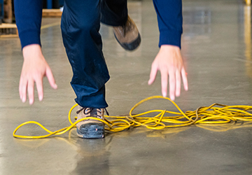 A worker's foot tangled up in an electrical cord.