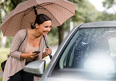 A woman outside the passenger side of a car confirming her ride.