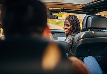 A woman in a car looking back at the passenger.