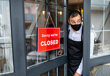 """""""Sorry we're closed"""" sign hung on the front door of a shop."""