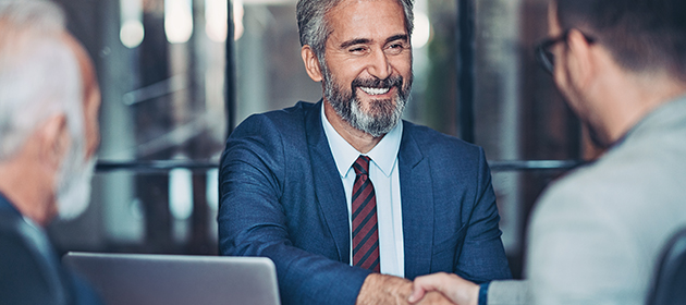 A male broker shaking hands with a client.