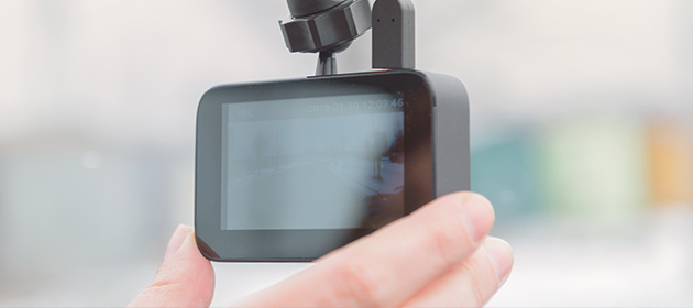 A person adjusting their dashboard camera.